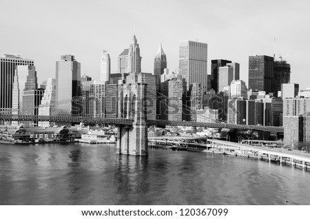 New York City skyline with Brooklyn Bridge and Lower Manhattan view in early morning sun light - Black and white