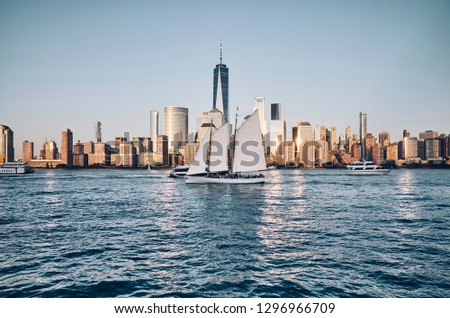 New York City skyline with busy Hudson River, color toned picture, USA.