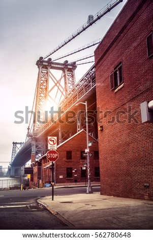 New York City street in Brooklyn with view to Williamsburg Bridge at sunset time. Old architecture buildings.
