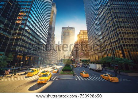 New York City street - Park Avenue view to Grand Central and skyscrapers. Busy street traffic with Taxis and Cabs in front. Sunny day and vibrant colors.