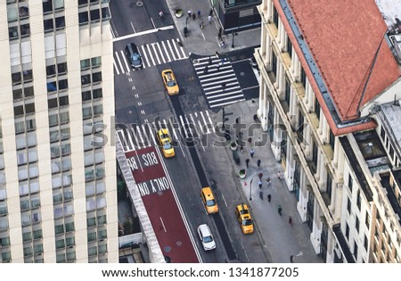New York city street with yellow taxis and people walking. Cabs, cars and pedestrians crossing crosswalk. Busy NYC Downtown traffic. Aerial view from above.