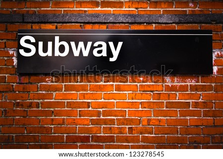 New York City subway sign entrance on brick wall