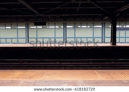 New York City subway train station late a night, no people  Waiting for a New York subway train in Brooklyn, green glass wall, standing on subway platform.