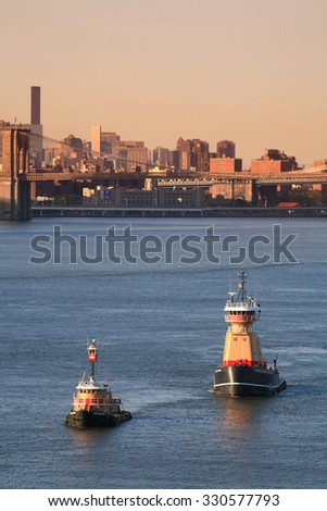 NEW YORK CITY, USA - APRIL 30 : A Meredith C. Reinauer tugboat and a Franklin Reinauer tugboat sailing in the East River with a view of the Brooklyn Bridge on April 30, 2006 in New York City, USA.