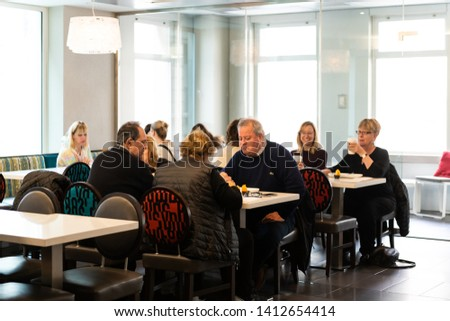 New York City, USA - April 6, 2018: Manhattan NYC building of midtown Herald Square Courtyard Marriott hotel with people sitting eating breakfast in restaurant