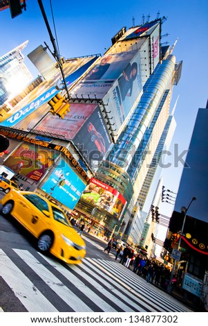 New York City, USA - Jan 6, 2013:  Yellow Taxi drives through Times Square in Midtown Manhattan on Jan 6, 2013. Times Square is a major commercial area known worldwide for it's lights and billboards. - stock photo