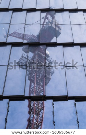 NEW YORK CITY, USA - JUNE 09 2016: A very high hoisting crane used for building skyscrapers mirrored in the glass and metal walls of a skyscraper