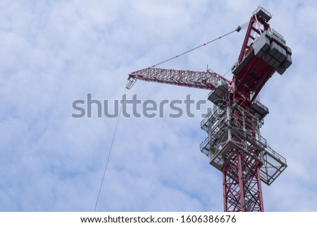 NEW YORK CITY, USA - JUNE 09 2016: A very high hoisting crane used for building skyscrapers against a cloudy blue sky