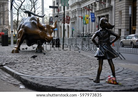 """New York City, USA - March 11, 2017: """"The Fearless Girl"""" statue facing the Charging Bull erected to honor International Women's Day in Lower Manhattan in New York City."""