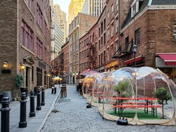 New York City, USA - November 26, 2020: Restaurants and bars enforce social distance safety with outdoor dining bubbles on Stone Street in Manhattan during the coronavirus pandemic.