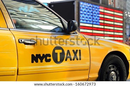 NEW YORK CITY, USA - November 14, 2012:Yellow cab taxi at Times Square in front of the USA national flag. November 14,2012 New York