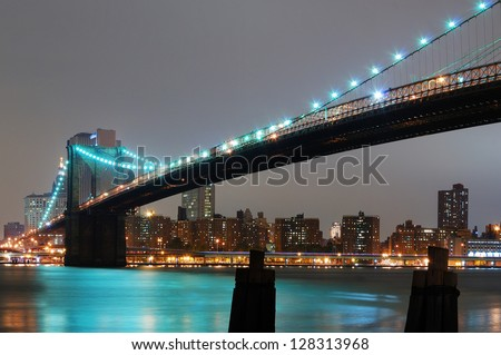 New York City with Brooklyn Bridge at night over Hudson River.