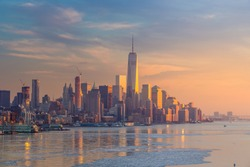 New York City with skyscrapers illuminated over Hudson River panorama, including the One World Trade Center