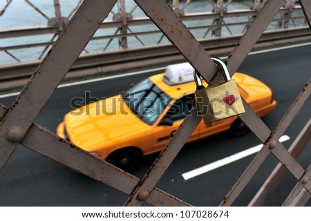 New York City yellow taxi cab drive pass by padlock with a heart symbol on Brooklyn Bridge in Manhattan New York, USA.