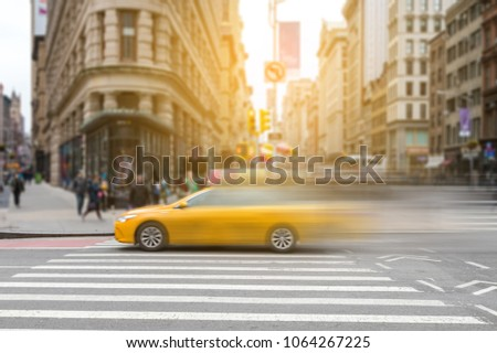 New York City yellow taxi cab in motion across broadway in Manhattan