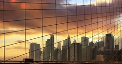 New York cityscape and Brooklyn Bridge cables, cloudy sky at sunset background. Manhattan United states of America
