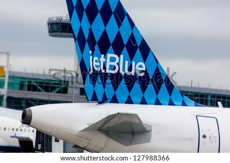 NEW YORK - DECEMBER 9: Airbus A320 JetBlue tailfin Harlequinon design on JFK airport in New York USA on December 9, 2012 JetBlue aircrafts feature one of several tail designs and name with word blue