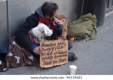 NEW YORK - FEBRUARY 25: A homeless man sitting on the street with a dog and asking for help February 25, 2012 in New York City. - stock photo
