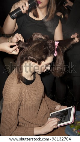 NEW YORK - FEBRUARY 11: Model prepares backstage for Vantan Tokyo collection while using Apple iPad surfing Internet during Fashion week at Lincoln Center in Manhattan on Feb 11, 2012 in New York City