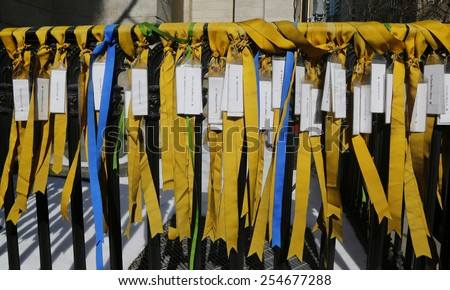 NEW YORK - FEBRUARY 19, 2015: Prayers for Peace Ribbons on the fence of the Marble Collegiate Church. Gold ribbons represents prayers for US service people lost their lives in Iraq and Afghanistan #254677288