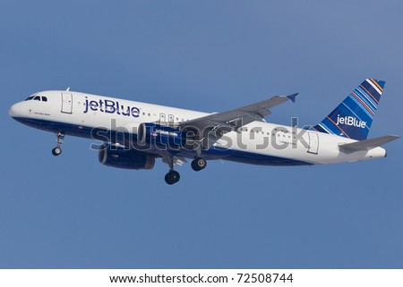 "NEW YORK - JANUARY 30: Airbus A320 of JetBlue Airlines, wearing new livery called ""barcode"" , on final approach to John F Kennedy International Airport on January 30, 2011 in New York, USA - stock photo"
