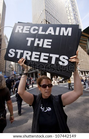 NEW YORK-JULY 11: A protester holds a sign that says 'Reclaim The Streets' at the Occupy Guitarmy march in Lower Manhattan during the #99MileMarch from Philly to NYC on July 11, 2012 in New York, NY.
