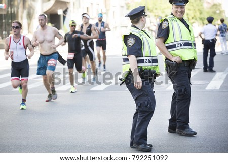 NEW YORK - JULY 16 2017: NYPD patrol the route on West 72nd St for athletes running the 10k portion of the Panasonic New York City Triathlon Race, the only International Distance triathlon in NYC. #792251092