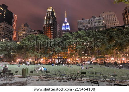NEW YORK - JULY 9, 2014: View of Bryant Park and Manhattan Skyscrapers at Night. People relaxing on the grass. #213464188