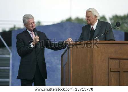 NEW YORK - JUNE 25: Former U.S. President Bill Clinton (L) speaks with Rev. Billy Graham while on stage at the Greater New York Billy Graham Crusade June 25, 2005 in Flushing, New York. - stock photo