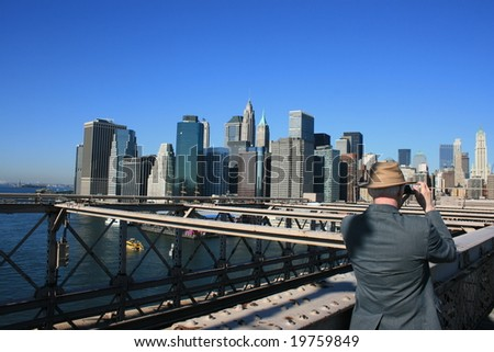 New York - Man taking photos of the Manhattan skyline from the Brooklyn Bridge, New York City, October 2008.