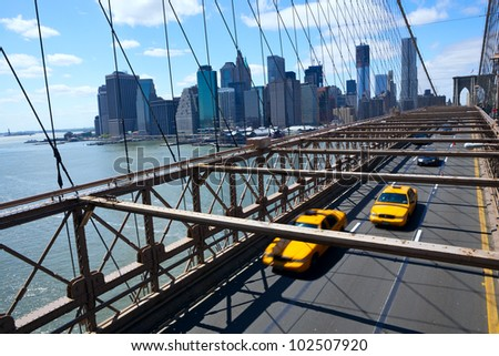 New York Manhattan skyline from the Brooklyn Bridge with yellow taxi's