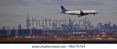 NEW YORK -MARCH 1: Airbus A320 Jet Blue airlines arriving on JFK Airport on Runaway 4L with Manhattan skyline in background on March 1, 2010 in New York. Picture taken from Bayswater Park