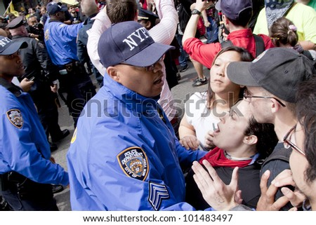 NEW YORK - MAY 1: Police attempt to guide angry protesters onto the sidewalk during the march to Union Square from Bryant Park during Occupy Wall St 'May Day' protests on May 1, 2012 in New York, NY.