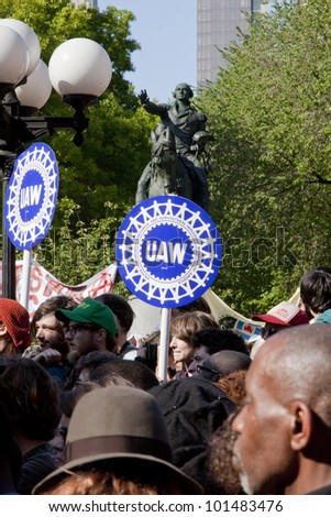 NEW YORK - MAY 1: Signs in support of the UAW union are held by protesters with a statue of George Washington in the background during May Day protests in Union Square on May 1, 2012 in New York, NY.