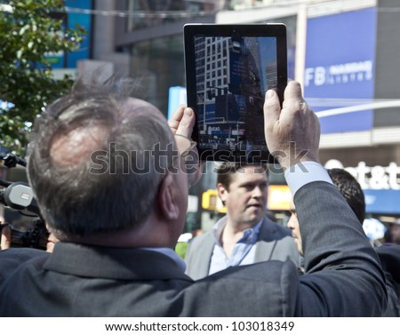 NEW YORK - MAY 18: Unidentified man takes picture with iPad of Facebook listed on NASDAQ stock exchange flashed on a screen of Thomson Reuters at the opening bell in Times Square on May 18 2012 in NYC - stock photo