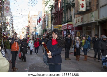 NEW YORK, NEW YORK - FEBRUARY 17: Young Asian woman tries out a Chinese firecracker during Chinese New Year Parade.  Taken February 17, 2013 in  NYC.