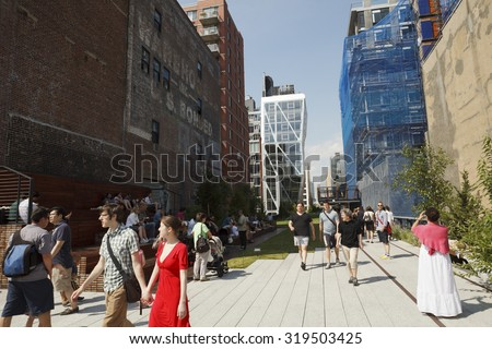 New York, New York, USA - June 20, 2011: People strolling along The High Line. The High Line is an NYC park located on what used to be an elevated rail line.