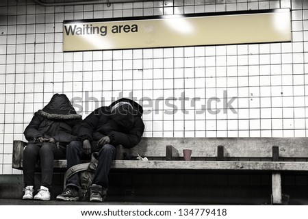 NEW YORK - NOV 14: People sitting on a bench at a subway station\'s waiting area, hidden behind their coats, on November 14 2012 in New York, New York.