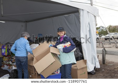 NEW YORK - NOV 12: Volunteers and workers helping people after Hurricane Sandy in  the flooded neighborhood at Breezy Point in Far Rockaway area  on November 12, 2012 in New York City, NY #118907761