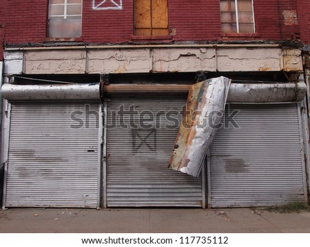 NEW YORK, NOVEMBER 3: Damaged metal doors cover closed stores on Front Street in New York City, November 3, 2012. Lower Manhattan was seriously damaged by flooding from Hurricane Sandy.