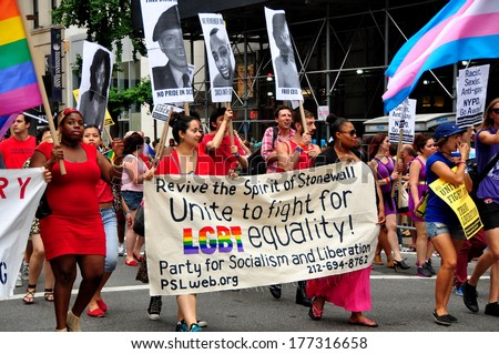 New York, NY - June 30, 2013:  Political group carrying banners, photos, and rainbow flags marching for LGBT equality at the Gay Pride Parade on Fifth Avenue