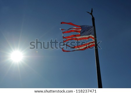 NEW YORK, NY - NOVEMBER 09: An American ripped flag flies from the front yard of a house in a damaged area November 9, 2012 in the Breezy Point part of Far Rockaway in the Queens borough of NY.