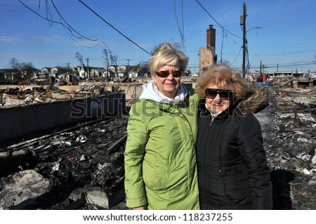 NEW YORK, NY - NOVEMBER 09: Local residents looking over to scenes of Hurricane Sandy's aftermath in the Breezy Point part of Far Rockaway on November 9, 2012 in the Queens borough of New York City.