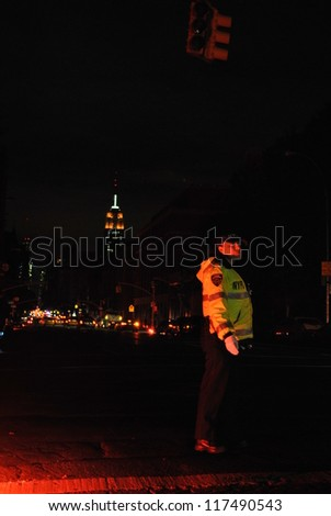 NEW YORK, NY - NOVEMBER 1: NYPD directs traffic on Sixth Ave in the West Village with Empire State building in background during the blackout caused by Hurricane Sandy on Nov 1st 2012 in New York.