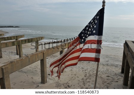 NEW YORK, NY - NOVEMBER 09: The destroyed boardwalk and a tattered American flag following Superstorm Sandy at Rockaway Beach on November 9, 2012 in the Queens borough of New York City.