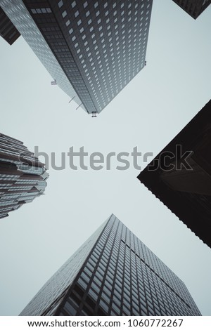 NEW YORK, NY - UNITED-STATES May 2017 - Four skyscraper buildings shot from below on a cloudy day. #1060772267