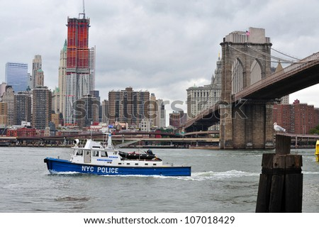 NEW YORK - OCT 18: American police boat (N.Y.P.D) patrolling under the Brooklyn Bridge and One World Trade Center on October 18, 2010 in Manhattan New York City, USA.