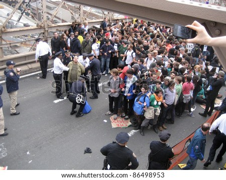 NEW YORK - October 1: A spectator snaps a camera phone picture as Occupy Wall Street protesters are arrested by police officers on the Brooklyn Bridge, October 1, 2011 in New York City.