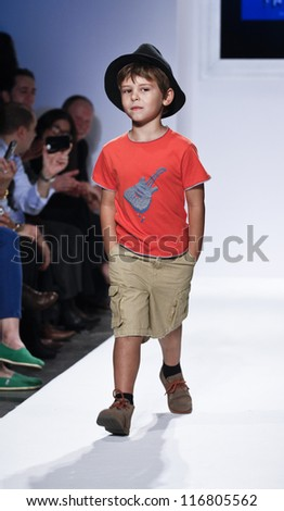 NEW YORK - OCTOBER 20: Boy model walks runway for petite Parade show collection by iNTAKT during kids fashion week NYC sponsored by Vogue Bambini at Industria Superstudio on October 20, 2012 in NYC