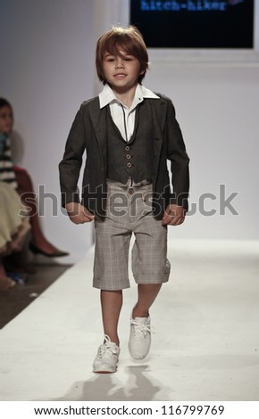 NEW YORK - OCTOBER 21: Boy walks runway for petite Parade show by Hitch-Hiker during kids fashion week sponsored by Vogue Bambini at Industria Superstudio on October 21, 2012 in New York City